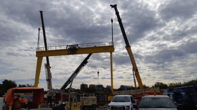 A picture showing a large yellow crane with blue sky in background and construction equipment around