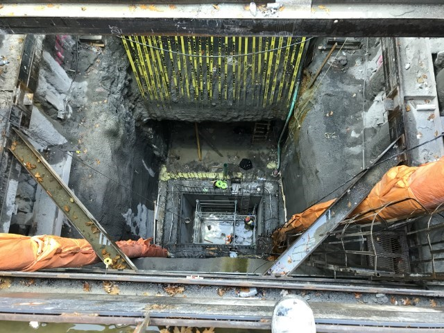 A picture showing construction at the bottom of a large underground shaft.