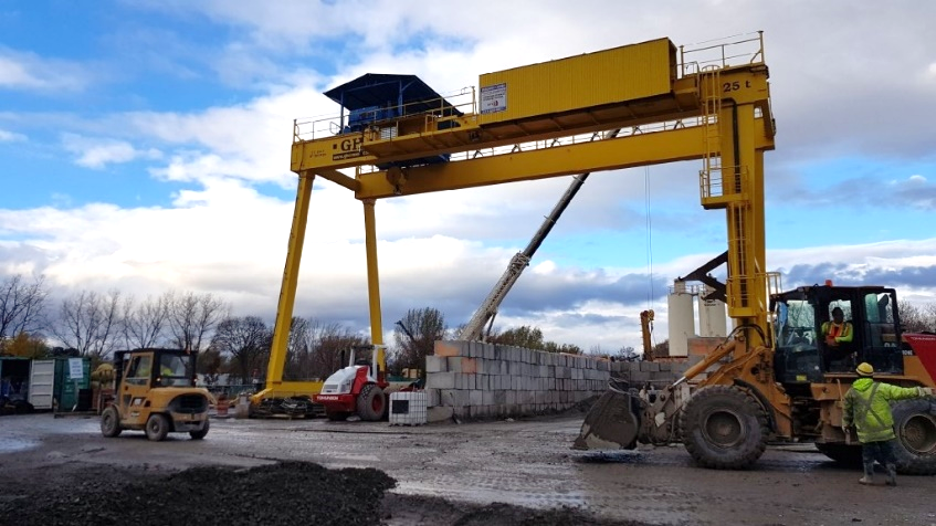A picture showing a large yellow structure and other construction machinery driving around site.