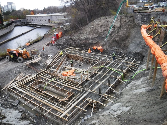 A picture showing a large area of ground covered with wood frame and concrete being poured into it.