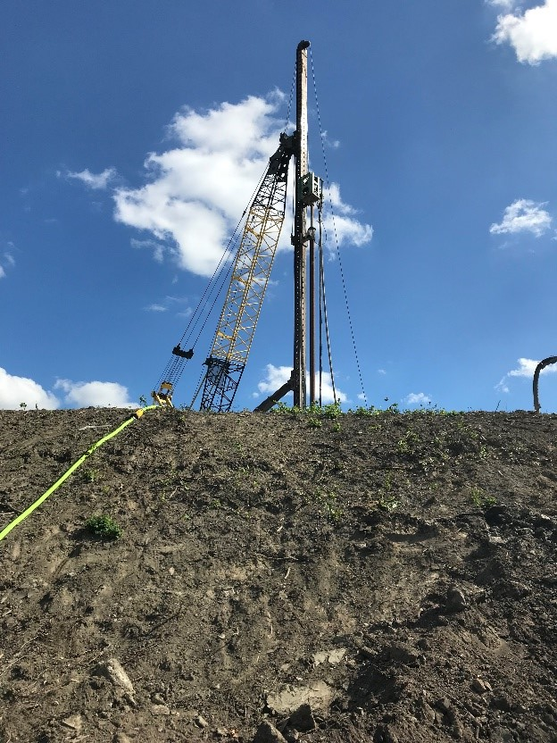 A picture of a hill and blue sky above with a tall piece of equipment operating at the top of the hill