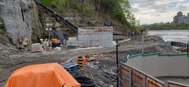 Picture showing a construction site containing a large concrete building and Ottawa River in the background.