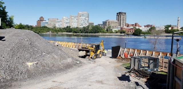 A picture looking at a construction site with a large rock pile to the left, yellow loader carrying rock in the background, and the Ottawa River and buildings beyond that.