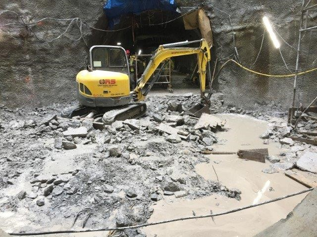 Picture of piece of construction machinery breaking concrete floor at the bottom of a large cylindrical shaft underground.