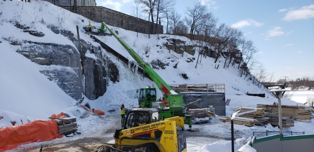 Picture showing construction equipment and concrete chamber beside a rock cliff.