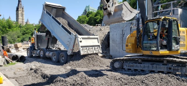A picture showing a dump truck dumping earth onto the ground with a large yellow machine adjacent to the pile and concrete structure in the background.