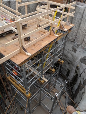 Picture showing underground construction work, with stacked steel beams and a wood platform on the top.