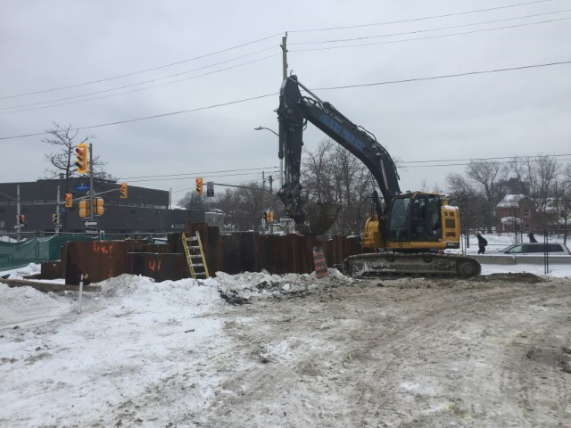 A picture showing a large piece of construction equipment removing dirt from inside a rectangular fence.