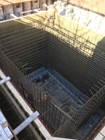 Picture showing inside of a large rectangular underground shaft showing a series of steel along in the inside perimeter.