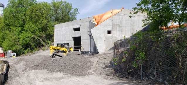 Picture of a large concrete building with construction machinery in front.