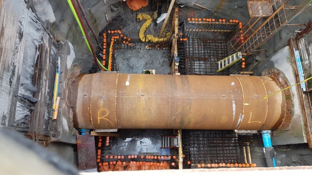 Picture showing a large pipe across the bottom of a large concrete cylindrical shaft with steel being built up around it.