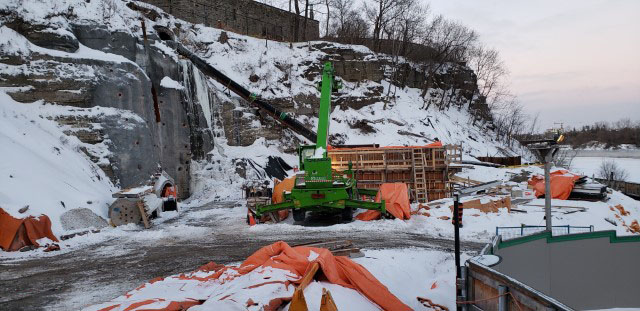 A picture of a rock cliff, showing a piece of green construction machinery working on a wood structure, on a snow covered ground
