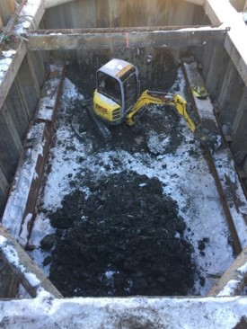 A picture of excavation of a rectangular shaft below the surface and piece of construction equipment.