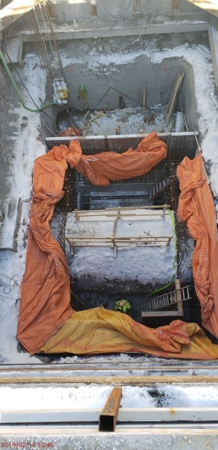 Picture of construction at the bottom of a large rectangular shaped hole below ground.