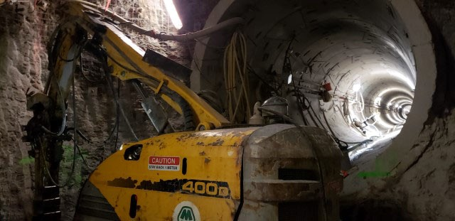 Picture inside of a underground chamber with a piece of construction equipment and inside of a large concrete pipe in the distance.