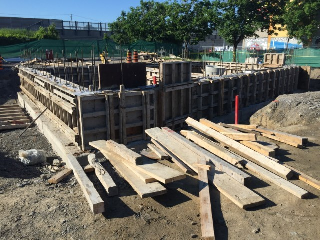 A photo showing a rectangular wall structure made of wood, for a building foundation, above ground.