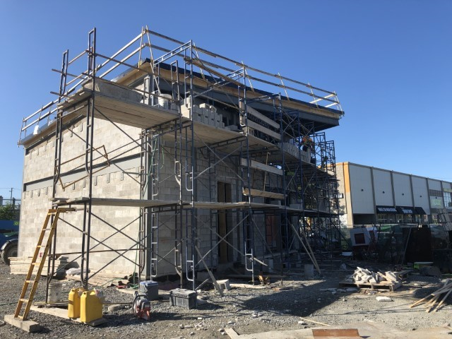 A picture showing a concrete building being constructed, with steel and wood scaffolding erected around it.