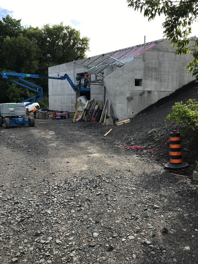 A picture showing a small concrete building being built beside a gravel path.