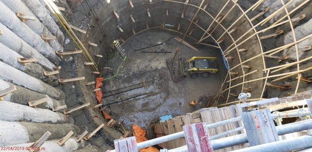 Picture of a large cylindrical underground shaft showing construction equipment moving dirt at the bottom and wood formwork along the inside walls.