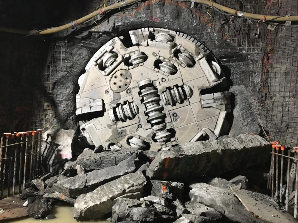 A picture of a large cylindrical machine with cutter wheels emerging from a rock face.