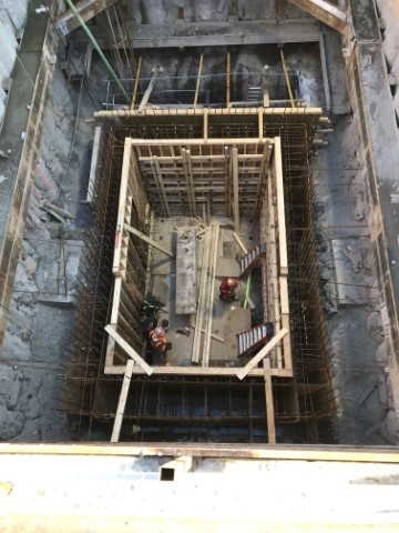 Picture looking into a large rectangular shaft below ground with a wooden structure being built along its interior.