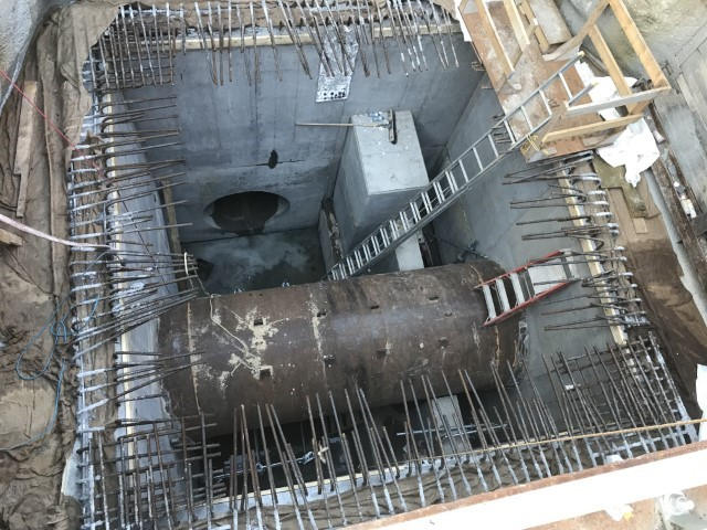 A picture looking down into a large rectangular underground shaft showing a concrete pipe going across the middle and a series of metal rods along the top.